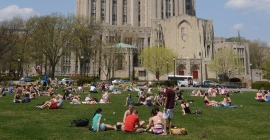 Students gather on the lawn in Schenley Plaza outside of the Cathedral of Learning.